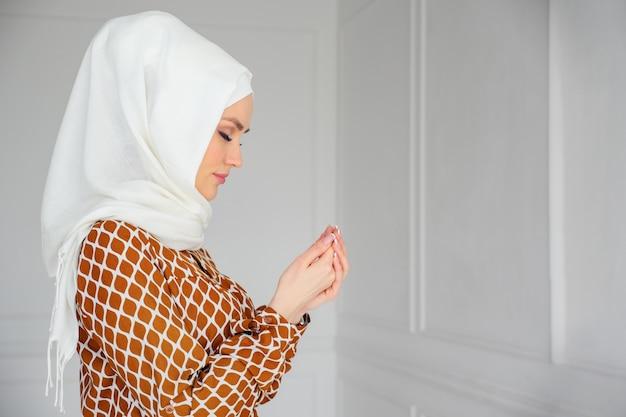 Retrato de uma jovem mulher muçulmana em hijab branco e vestido tradicional, rezando, copie o espaço.