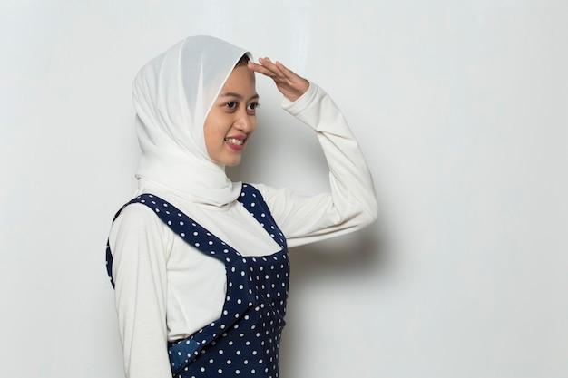 Retrato de uma jovem mulher muçulmana muito curiosa espiando por entre os dedos como um binóculo Foto Premium
