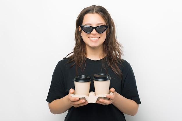 Retrato de uma jovem mulher na moda com óculos escuros, sorrindo e segurando duas xícaras de café para viagem