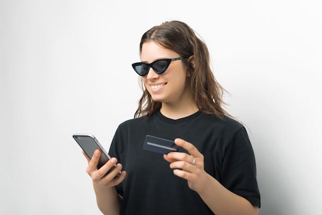 Retrato de uma jovem mulher na moda em camiseta preta, usando óculos escuros e usando smartphone com cartão de crédito