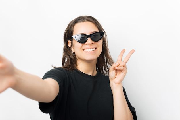 Retrato de uma jovem mulher na moda, usando óculos escuros, tomando selfie e mostrando um gesto de paz.