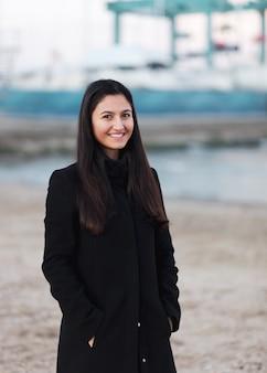 Retrato de uma jovem mulher na praia com roupas de inverno.
