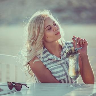 Retrato de uma jovem mulher no café na praia, bebendo coctail, imagens enfraquecidas.