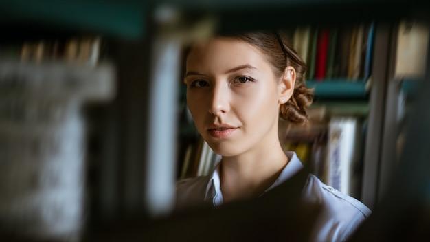 Retrato de uma jovem mulher no contexto de livros na biblioteca, olhando através das prateleiras dos livros. o conceito de preparação para os exames