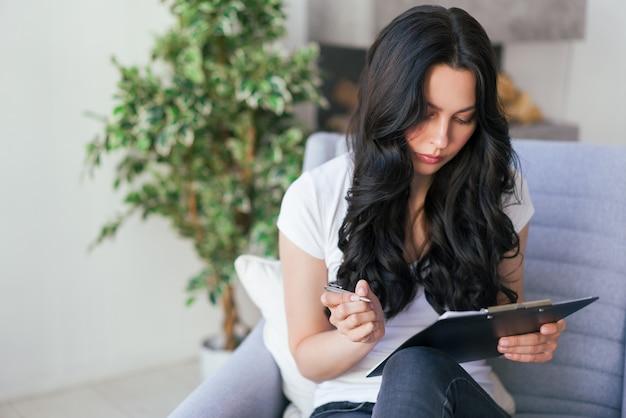 Retrato de uma jovem mulher no escritório. mulher grava dados no questionário.