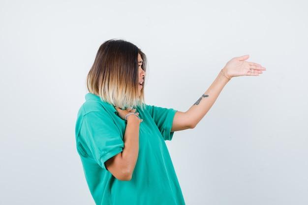 Retrato de uma jovem mulher oferecendo um aperto de mão, mantendo a mão no peito em uma camiseta polo e olhando perplexa com a vista frontal