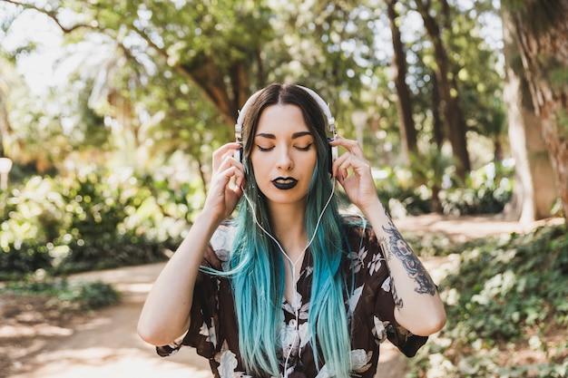 Retrato de uma jovem mulher ouvindo música no fone de ouvido