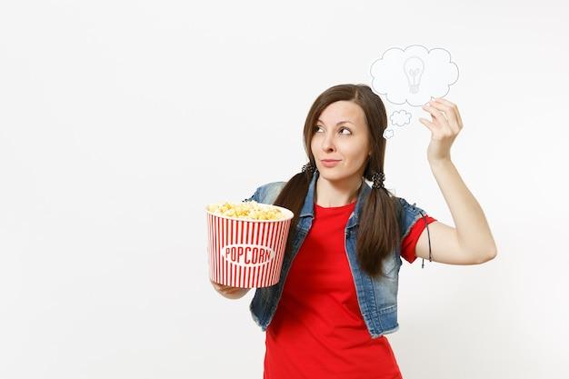 Retrato de uma jovem mulher pensativa em roupas casuais, assistindo a um filme, segurando, digamos, nuvem com lâmpada, ideia, balde de pipoca, isolado no fundo branco. emoções no conceito de cinema. balão de fala