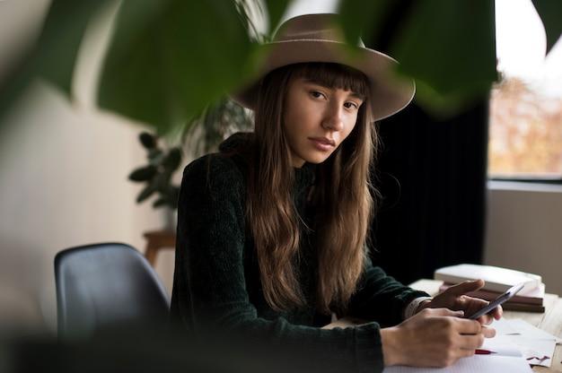 Retrato de uma jovem mulher pensativa no elegante chapéu segurando o telefone móvel, trabalhando em casa