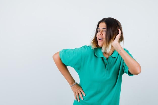 Retrato de uma jovem mulher posando, mantendo a mão na cabeça em uma camiseta polo e olhando de frente com alegria