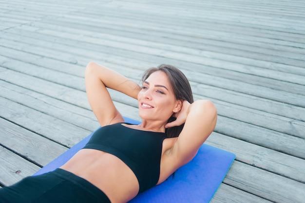 Retrato de uma jovem mulher praticando esportes fazendo exercícios para os músculos abdominais, deitada em uma esteira sobre tábuas de madeira ao ar livre