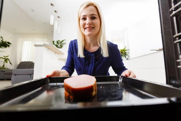 Retrato de uma jovem mulher preparando comida na cozinha. jovem dona de casa segurando carne recém-assada