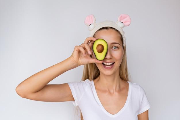 Retrato de uma jovem mulher que guarda o abacate fresco da mão perto de sua cara no branco.