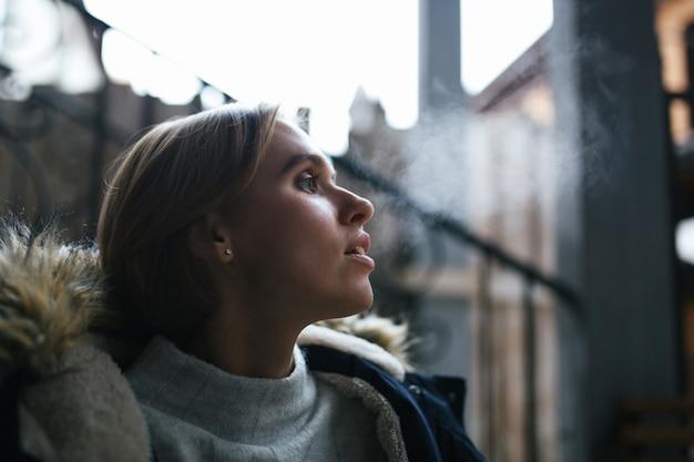 Retrato de uma jovem mulher que solta vapor de sua boca em um dia frio de inverno lá fora