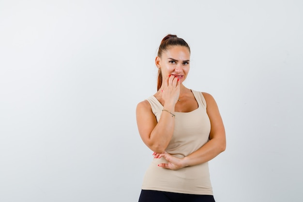 Retrato de uma jovem mulher roendo as unhas em um top bege e olhando pensativa para a frente