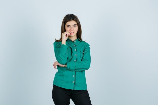 Retrato de uma jovem mulher roendo as unhas em uma camisa verde, calça e olhando pensativa para frente