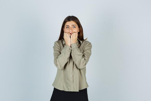 Retrato de uma jovem mulher roendo as unhas emocionalmente na camisa, saia e parecendo assustada com a vista frontal