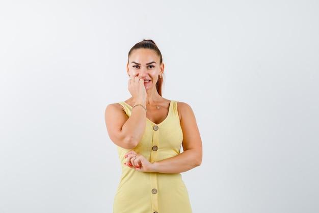 Retrato de uma jovem mulher roendo unhas emocionalmente em um vestido amarelo e olhando animada para a frente