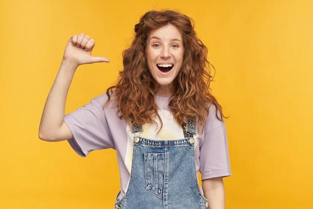 Retrato de uma jovem mulher ruiva positiva, usa macacão azul e camiseta roxa, sorri amplamente, divirta-se, apontando com o dedo para si mesma isolada sobre a parede amarela