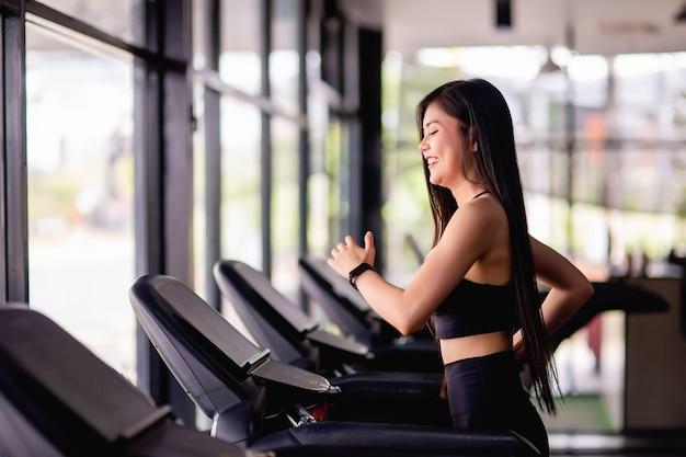 Retrato de uma jovem mulher saudável correndo na esteira, ela sorri durante um treino na academia, conceito de estilo de vida saudável, imagem vertical do espaço de cópia