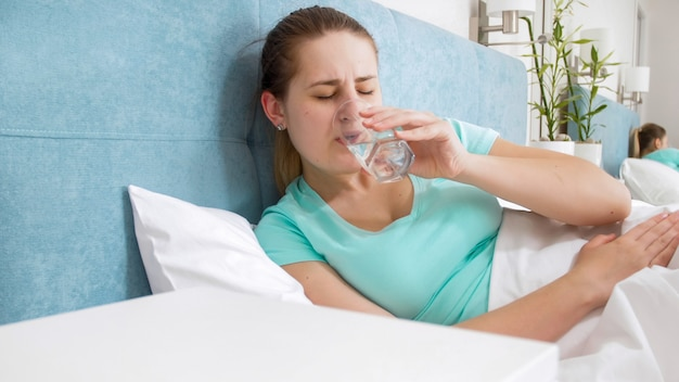 Retrato de uma jovem mulher se sentindo mal, deitada na cama em casa e bebendo água.