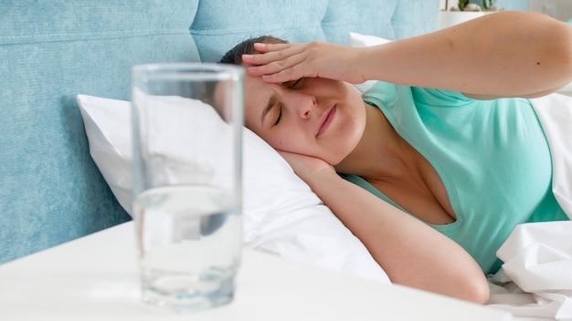 Retrato de uma jovem mulher se sentindo mal, sofrendo de dor de cabeça, deitada na cama.
