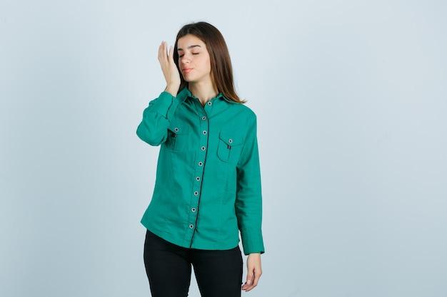 Retrato de uma jovem mulher segurando a palma da mão na frente do rosto em uma camisa verde, calça e olhando encantado para a frente