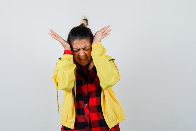 Retrato de uma jovem mulher segurando as mãos na cabeça em uma camisa quadriculada, jaqueta e com uma vista frontal dolorida