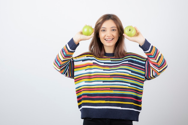 Retrato de uma jovem mulher segurando duas maçãs verdes frescas.