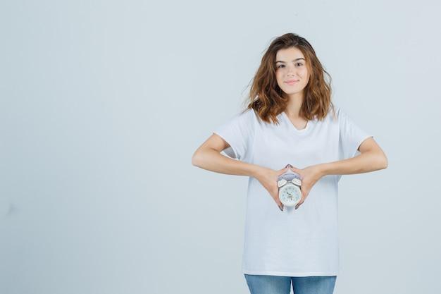 Retrato de uma jovem mulher segurando o despertador em uma camiseta branca, jeans e olhando alegre para a frente