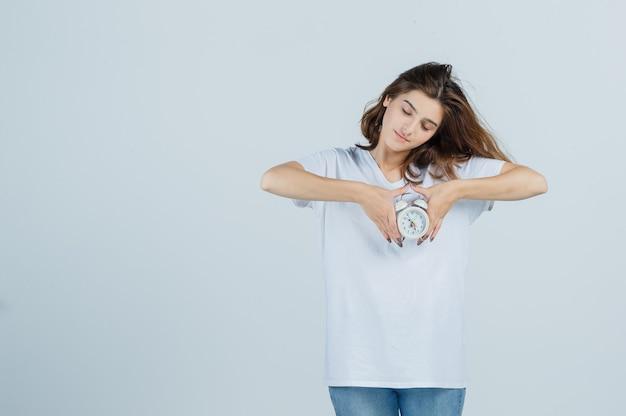 Retrato de uma jovem mulher segurando o despertador em uma camiseta branca, jeans e olhando graciosa de frente