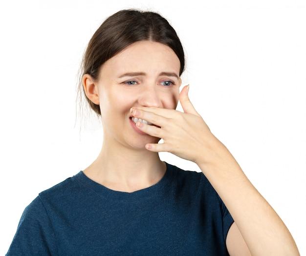 Retrato de uma jovem mulher, segurando o nariz por causa de um mau cheiro.