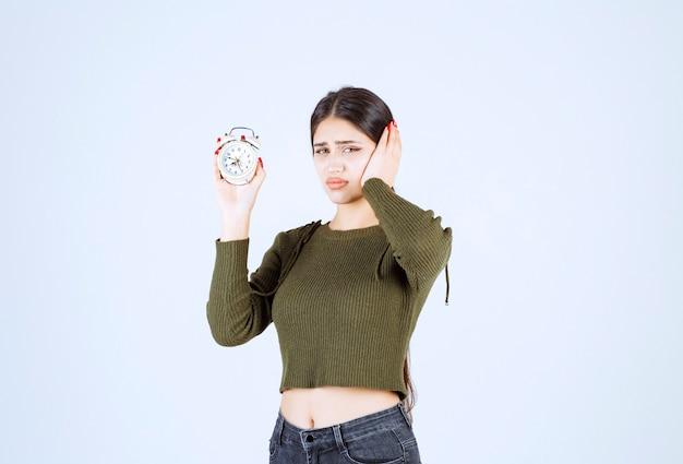 Retrato de uma jovem mulher segurando o relógio despertador com expressão louca.