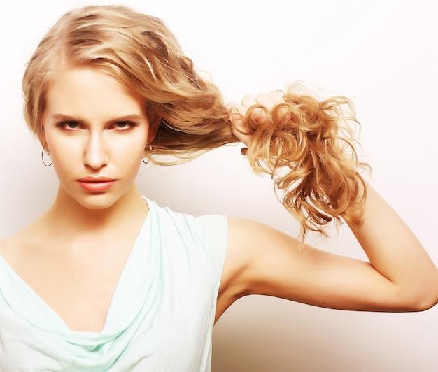 Retrato de uma jovem mulher segurando seu cabelo longo e encaracolado