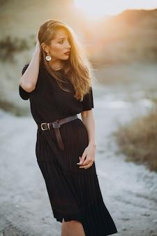 Retrato de uma jovem mulher sensual em um pôr do sol
