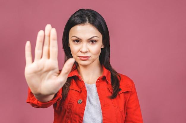 Retrato de uma jovem mulher séria que está com a mão estendido que mostra o sinal do gesto da parada isolado sobre a parede cor-de-rosa.