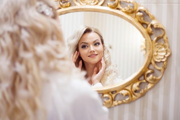 Retrato de uma jovem mulher sexy em um roupão, olhando no espelho.