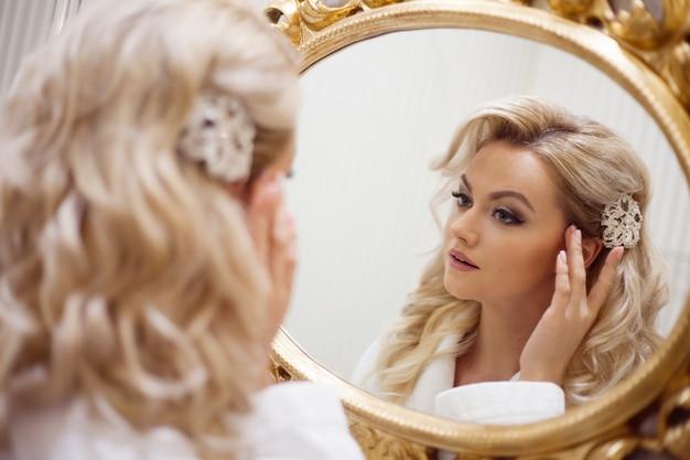 Retrato de uma jovem mulher sexy em um vestido branco, olhando no espelho.