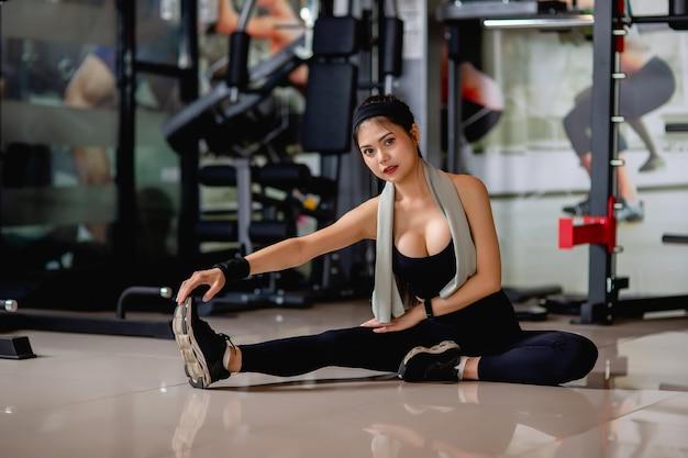 Retrato de uma jovem mulher sexy vestindo roupas esportivas e smartwatch, sentada no chão e alongando os músculos das pernas antes do treino no ginásio de fitness,