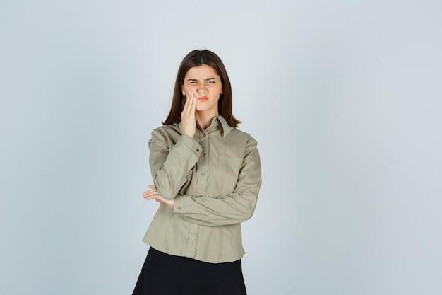 Retrato de uma jovem mulher sofrendo de dor de dente na camisa