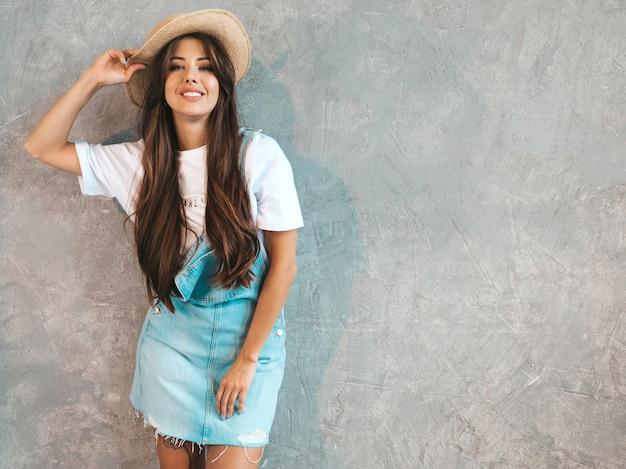 Retrato de uma jovem mulher sorridente bonita olhando. menina na moda em roupas de verão casual macacão e chapéu.
