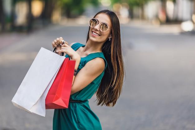 Retrato de uma jovem mulher sorridente feliz com sacos de compras, desfrutando de compras. emoções positivas.