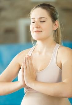 Retrato de uma jovem mulher sorridente meditando