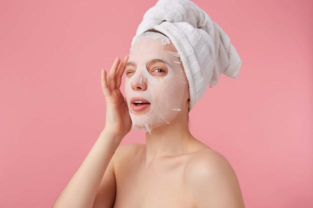 Retrato de uma jovem mulher sorridente positiva após spa com uma toalha na cabeça, com máscara para o rosto, goza de tempo para autocuidado, piscadelas, parece carrinhos.