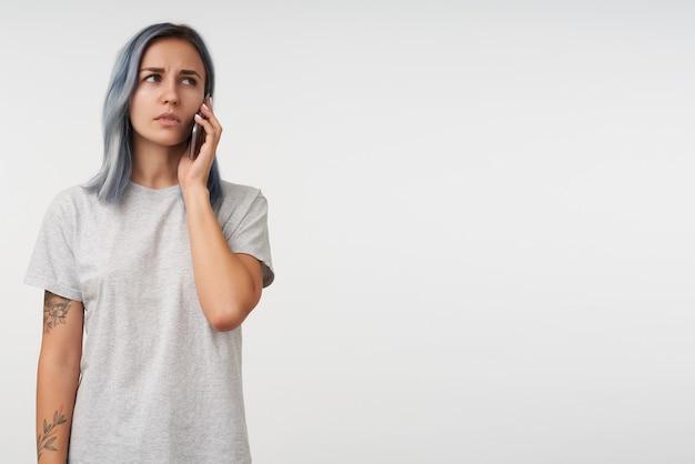 Retrato de uma jovem mulher tatuada séria com cabelo curto azul, mantendo o celular na mão levantada enquanto conversa ao telefone, isolado no branco