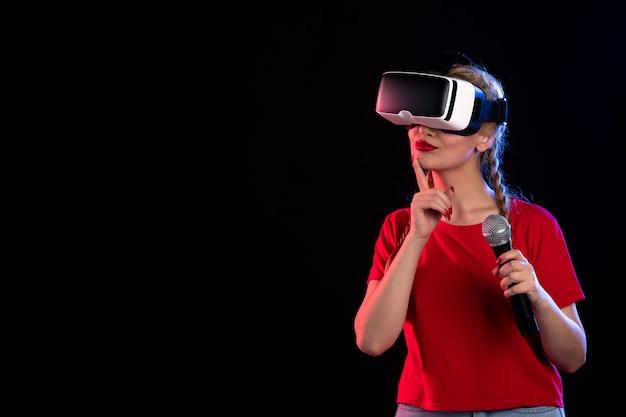 Retrato de uma jovem mulher tocando vr e cantando com o microfone do jogo de música dark