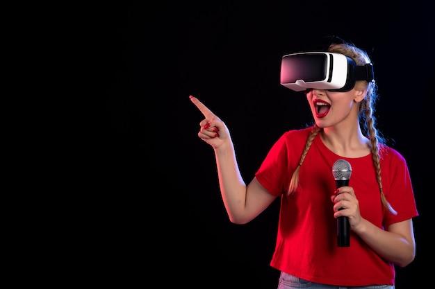 Retrato de uma jovem mulher tocando vr e cantando com o microfone na música dark do jogo visual