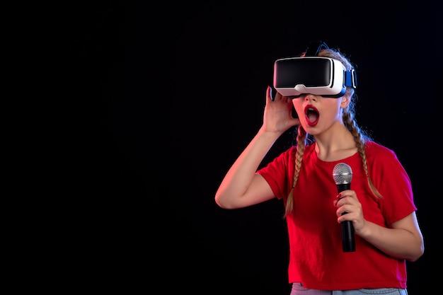 Retrato de uma jovem mulher tocando vr e cantando com o microfone no visual de jogo de música dark d