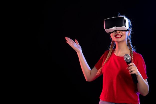 Retrato de uma jovem mulher tocando vr e cantando com um jogo de música visual escuro de microfone