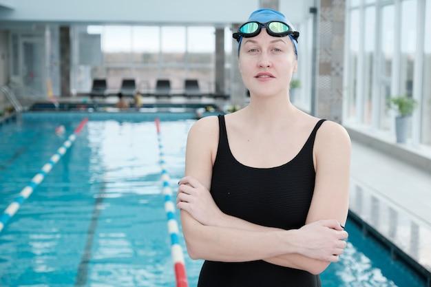 Retrato de uma jovem nadadora confiante sorridente com óculos e boné em pé com os braços cruzados contra a piscina